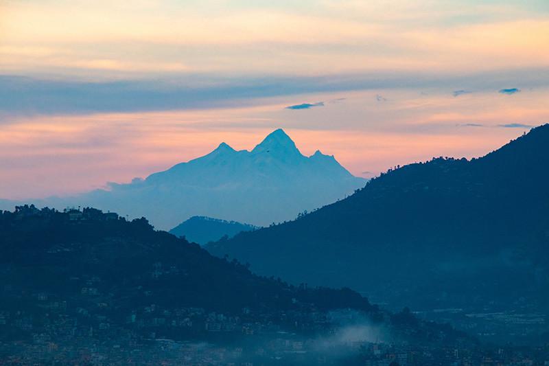 काठमाडौंको पश्चिममा बौद्ध हिमाल, हिमालचुली र मलास्लुको साथमा काठमाडौंबाट देखिएको सूर्यास्त ।